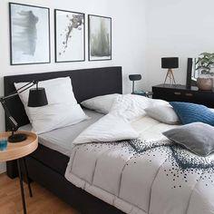 Sie wollen zur Ruhe kommen? In unserem coolen Schlafzimmer können Sie genau das! Großflächiges Schwarz – wie Bett und Kommode – gibt dem Raum stille Klarheit. Originelle Drehs nehmen ihm die Kühle: Setzen Sie Highlights mit abstrakter Kunst, verschiedenen Lampenformen und gestreiftem Wäschekorb. Und für den Kuschelfaktor: warme Holzakzente und weiche Fleecekissen.