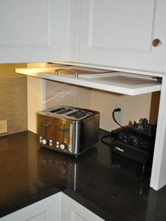 A white Shaker-style cabinet appliance garage hides appliances when not in use to give the kitchen a clean and crisp look. The dark stone countertops provide beautiful contrast against the bright white cabinetry. Kitchen Corner, Eat In Kitchen, Kitchen Redo, Kitchen Remodel, Kitchen Ideas, Corner Nook, Kitchen Small, Updated Kitchen, Corner Cupboard