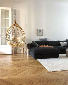 Wohnzimmer mit Hängesessel, schwarzer Couch, weißem Teppich und Fischgrätenparkett