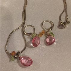 Silver & pink Crystal pendant and earrings set. A lovely silver necklace with a pink Crystal pendant. Small accent crystals of green and orange offset the larger stone. Matching earrings included with the set. Jewelry Necklaces