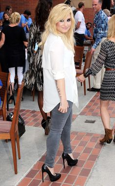 Demi Lovato looks casual chic in a white top, jeans, and black heels.