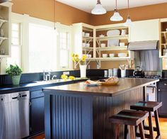 Mix Old and New- This Craftsman-style kitchen features a few modern touches such as stainless-steel appliances and sleek lighting, but period-specific trim and warm wood floors fit with the rest of the home. Cabinetry on the bottom half of the kitchen was painted a deep forest green; light paint on the upper shelves keeps the room from becoming too dark.
