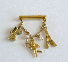 Vintage Chatelaine Brooch with Charms  Vintage chatelaine brooch featuring three charms and some faux pearls. The charms represent an old antique automobile, a cherub and the Eiffel Tower. There are two small faux pearls on each side of the cherub and has an open C clasp which makes it quite old.