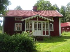 Traditional old Swedish house in the country in red with white trims and a glassed front porch.