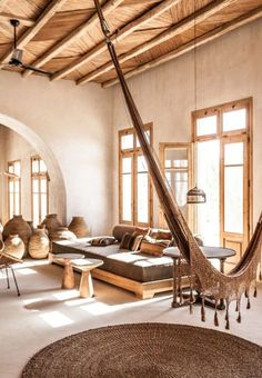 neutral living room | indoor hammock | brown living room | exposed wood | round sisal rug | pots | windows | home decor inspiration