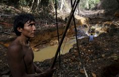 A Yanomami Indian stands near an illegal gold mine during an environmental agency operation in Roraima state on April 17, 2016