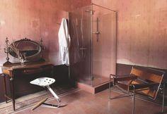 """Cette salle de bains était à l'origine un petit salon. Pour ne faire qu'un avec le sol et les murs anciens, le bac à douche a été réalisé en poudre et écailles de marbre. Devant, tabouret """"Mezzadro"""" d'Achille Castiglioni (Zanotta) et fauteuil """"Wassily"""" de Marcel Breuer."""