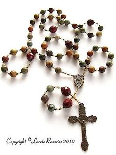 This woman's bronze rosary is made with 8mm Red Creek Jasper gemstone beads. Red Creek Jasper beads have gorgeous combinations of tan, red, and sage greens. Paters are 10mm faceted Mookite Jasper beads. The rosary center is 3/4 inches long with Our Lady on one side and Our Lord on the other side and the Angels Crucifix is 2 inches long. They are solid bronze and are hand cast from antique vintage pieces. One of a kind original creation.