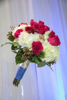 White hydrangeas with hot pink roses and hot pink spray roses with seeded eucalyptus and lemon leaves.  Great for blue color Bride's maid dress.