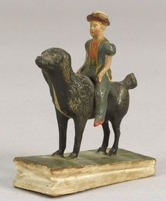 Boy and Dog Polychrome Painted Papier-maché Squeak Toy, probably Germany, late 19th century, the figure of the boy is seated atop a large black and white dog, ht. 4 1/4, lg. 3 1/2 in.   Sold for $ 1,410