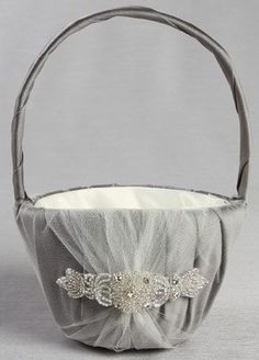 """Wrapped in delicate ivory tulle gathered over rich champagne satin, this flower girl basket is an elegant yet classic design. An elaborate rhinestone and beaded applique is the perfect embellishment for this radiant vintage style basket. Features and Facts: Dimensions: 9.5"""" H. Inner basket: 5"""" W x 3.5"""" D Made of satin and tulle with rhinestone and silver bead embellishment"""