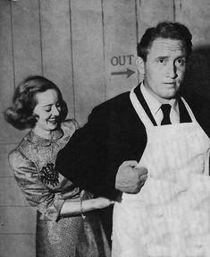 Bette Davis helps Spencer Tracy don an apron at the Hollywood Canteen.