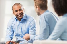 Smiling African American businessman talking to his colleagues. stock photo