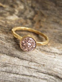 Gorgeous, rose gold colored druzy quartz stone is set inside a petite 18K gold vermeil hammered ring band. Natural, druzy stone is vapor coated with titanium to bring out a brilliant, consistent rose gold color. Druzy is 6mm round and unbelievably sparkly. 18K gold vermeil ring setting is made of sterling silver that has been heavily plated with 2 microns of pure 18K gold--a far more substantial layer than traditional plating. It features a thin hammered shank available in your choice of…