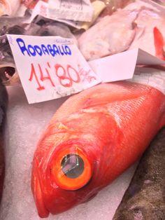 En el mercado, hay un pescado rojo que tiene ojos grandes. El pescado cuesta 14.80 euros.