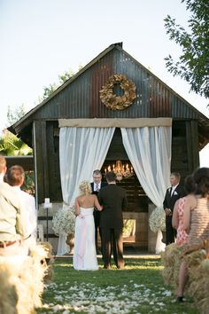 barn entrance decor - with drapery and small flowers/trees on either side of drapery