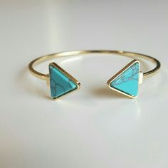 "Turquoise gold bangle This lovely 14k gold plated bangle has two triangles pointing towards eacg other and has cut and polished natural turquoise stone. This bracelet shows some signs of wear on the gold back part shown in the third picture, just minor chips. Still a lot of used and not noticable when worn.  This bracelet is adjustable and is 8"" in the pictures.  Great with your favorite shirt and jeans. Jewelry Bracelets"