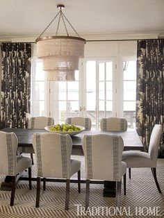 Neutral colors and delightful patterns play up the magnificent ocean views in this sophisticated dining room. - Traditional Home ® / Photo: Tria Giovan / Design: Ken Gemes