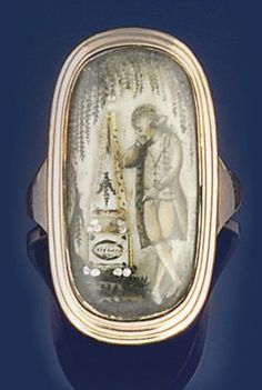A late 18th century gold mourning ring  The oval bezel with glazed sepia miniature depicting a gentleman mourner standing beside a sepulchral monument beneath a willow tree, within reeded border, the reverse engraved McCorrish, Obt. 29th December 1789 Aet. 30
