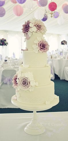 purple and ivory wedding cake with roses and hydrangeas