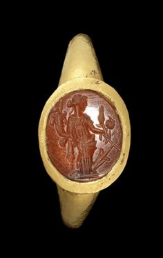 A Roman gold and carnelian intaglio ring  Circa 2nd-3rd Century A.D. The oval ringstone engraved with a standing profile figure of Fortuna holding a cornucopia, set in a Roman gold ring