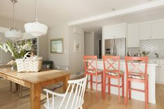 As seen on Love It or List It, Too, designer Jillian Harris was inspired by Scandinavian design for Kelly and Steve's kitchen remodel. She used clean lines, ample amounts of white, and small pops of subdued color throughout the space. She gave the family plenty of seating with the breakfast bar and the large farmhouse style table in the dining area just off the kitchen.