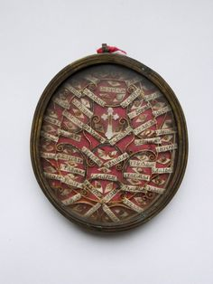 Reliqaury locket; brass; oval; glass containing relics of the saints, each bearing paper labels with with their origin, in ornamental compartments; red cloth background; suspension loop.