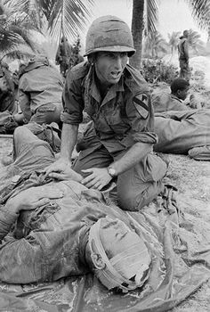 """Feb 4th, 1966 - Anguish crosses the face of this busy Medic shouting for a stretcher team as he treats a wounded soldier of the U.S. 1st Cavalry Division near Bong Son. The trooper was hit by enemy fire during """"Operation Masher,"""" 300 miles northeast of Saigon. The sweep by American forces killed a reported 325 Viet Cong and North Vietnamese regulars. - Bettmann/CORBIS ~ Vietnam War"""
