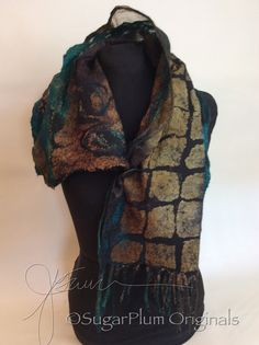 This scarflette (shorter version of a scarf) made out of silk habotai, shimmering thai silk and hand dyed silk organza with a very thin layer of black merino wool in the middle. There are also quite a few ruffles along the edges and has nuno cording at one end the other end has a unique hand dyed coconut button. The technique is called nuno Felting or laminating wool and silk after many hours of working the fibers you get the end result which is a ruched effect but is light and airy since I…