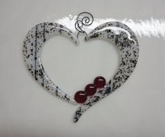 A pretty heart with a whimsical flair! Three bright red, shiny glass nuggets amplify the beauty of the black and white glass. A curly handcrafted