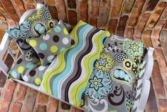 """A unique combination of Floral decor in green, gray, brown and teal adorn this 18"""" doll bedding set. The reverse side is a coordinating stripe covering all of the colors. Set includes dimpled polka do"""