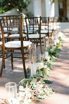 The wedding aisle is lined in greenery and pillar candles for a romantic feel.