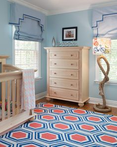 Light wood furniture is a smart, neutral choice for a nursery since it can grow with the child. A mod orange-and-blue area rug adds contemporary style underfoot, while elegant blue valances and shades blend beautifully into the walls. Accessories, like the floor lamp, showcase the parents' avid love of cycling.