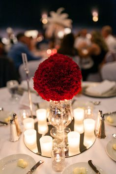 Gatsby Glam theme for these red carnation pomander style centerpieces in silver mercury glass with votive candles in frosted glass with pearls and mirror.  Thank you Hannah Smith Events.