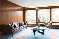 The pillows on the couch were homemade using vintage Maharam Eames dot fabric. A vintage Noguchi table sits underneath the owner's biggest splurge: A vintage Castiglioni Arco lamp. A Herman Miller fiberglass armchair sits close by. Table Basse Noguchi, Interior Design Inspiration, Home Interior Design, Pink Bathroom Decor, Dining Room Paint, Vintage House Plans, Formal Living Rooms, Living Spaces, Mid Century House