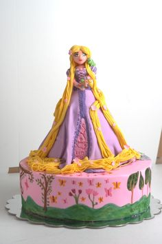 I made this cake for my daughters sixth birthday. The head and bodice are hand-scultpted fondant/gumpaste blend, the dress is cake, and, then, of course, cake below. The bottom tier was painted to resemble the artwork Rapunzel painted inside her tower. I also decorated the tier with a brick portion to represent the tower wall (sort of like you were seeing part inside/part outside of the tower). Other touches include a tiny Pascal on Rapunzels shoulder, and Rapunzel herself is holding a…