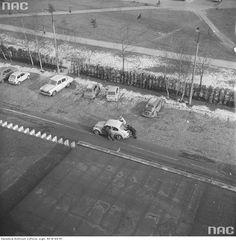 Przepychanie samochodu Volkswagen Garbus na osiedlowym parkingu. Widoczne zaparkowane samochody Fiat 126p oraz GAZ-21 Wołga. Widok z budynku Zjednoczonego Stronnictwa Ludowego przy ul. Grzybowskiej.