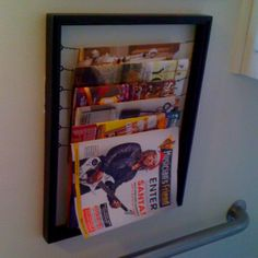 Magazine rack made from an old frame. I used hanging wire to make the magazine holders, and then painted the whole thing with black paint.  Hung with Velcro command strips (I recommend the black command strips).