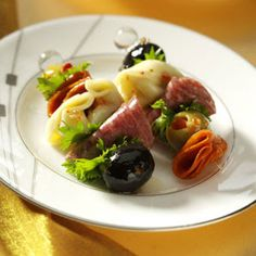 1 package (9 ounces) refrigerated cheese tortellini 40 pimiento-stuffed olives 40 large pitted ripe olives 3/4 cup Italian salad dressing 40 thin slices pepperoni 20 thin slices hard salami, halved Fresh parsley sprigs, optional