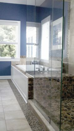 Bathroom with a big tub in a Glazed Autumn Mosaic tile (river-rock tile) deck and heavy glass shower enclosure