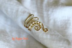 """A unique spin on a classic style, this ear cuff features freshwater pearls and measures approximately 3/4"""" tall, and a 1/2"""" wide.  Available in 14k Gold-filled, Sterling Silver, Copper or 14k Rose Gold-filled wire.    Called, """"The Half Swirl"""", the curved lines of this cuff follow the shape of you..."""