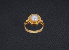 Handmade ring in 22k yellow gold. The natural gem in this design is a genuine Akoya cultered pearl (7 ml) of exceptional quality and exhibits