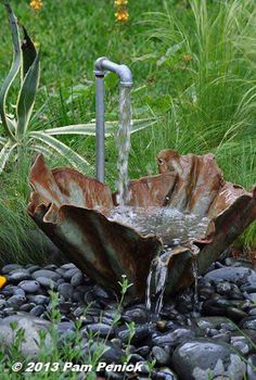Quirky and delightful industrial water feature for the backyard: a regular pipe and a folded piece of metal that looks like cloth.