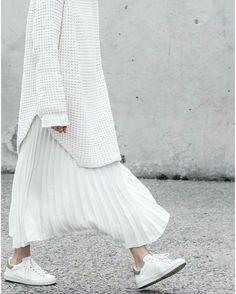 Un pull blanc avec une jupe plissée et des sneakers blanches