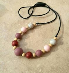 Baby wearing, teething necklace.   https://www.etsy.com/uk/listing/557808293/new-baby-gift-whitewood-and-silicone