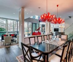 This Toronto dining room has a dark dining table, white and black chairs, a red piano, glass railings and dual red light fixtures.