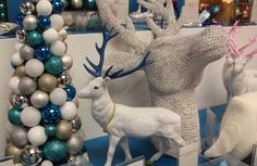 Group of Christmas decorations:  luxurious bauble tree in teal, gold, silver and blue;  white reindeer with sparkly blue antlers;   and oversized sparkling reindeer head.