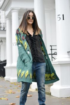 Anisa Sojka styles green knitted wool and alpaca blend Samsøe & Samsøe long cardigan | Black Oui ruched blouse | Blue denim girlfriend jeans | Black and gold Rayban classic round sunglasses | Black pointed stiletto heels | Levelled straight hairstyle | Fashion blogger street style shot in London by David Nyanzi