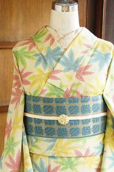 芥子色のこまかな絣模様がアクセントになったクリームイエローの地に、赤や青、緑や黄色など色とりどりのヤツデのような葉模様が織り出されたウールの単着物です。
