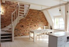 Attic renovation, wooden stairs white-washed, brick wall, grey kitchen